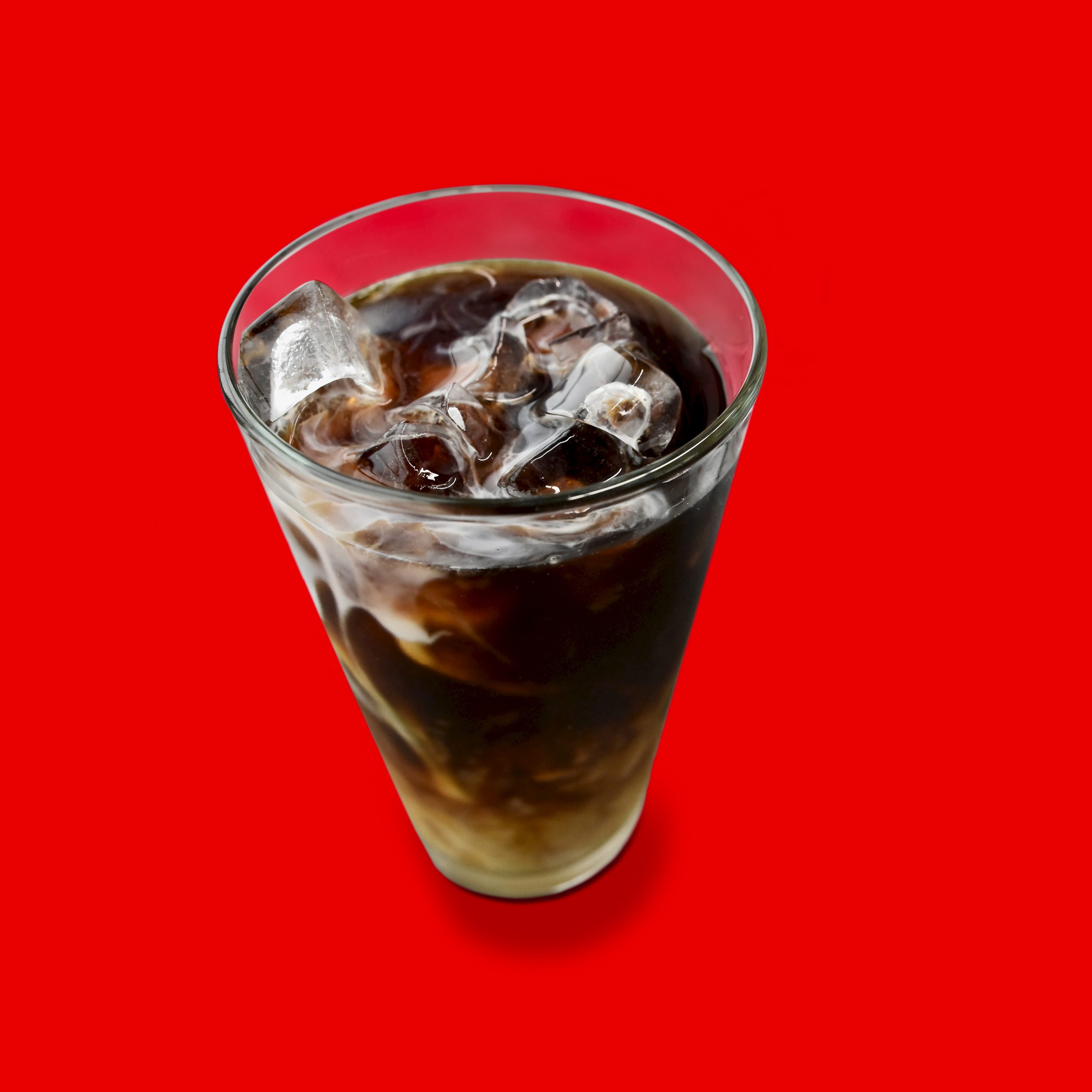 Iced Coffee in glass with ice on red background