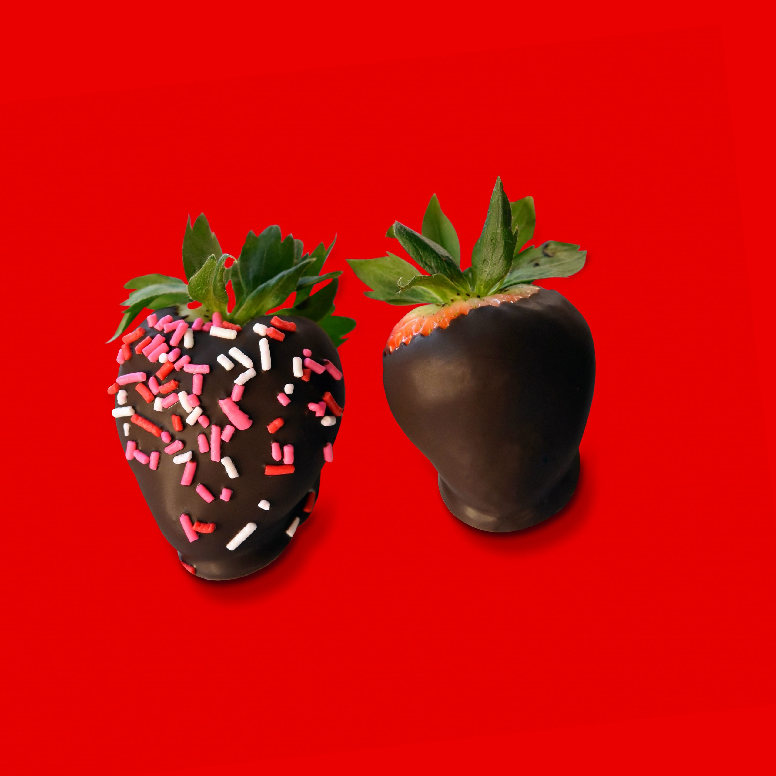 Two chocolate covered strawberries with sprinkles over read background