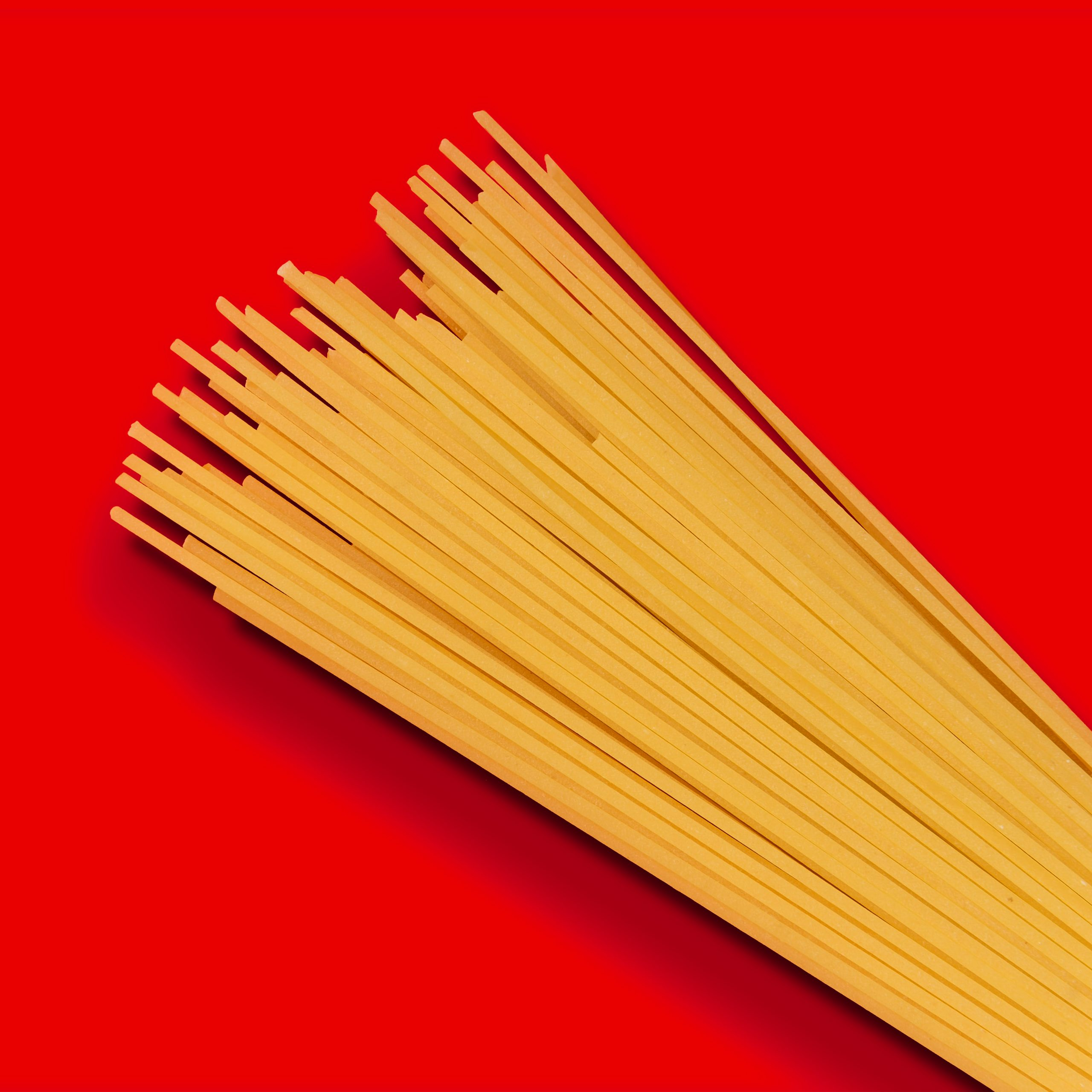 Dry pasta over red background