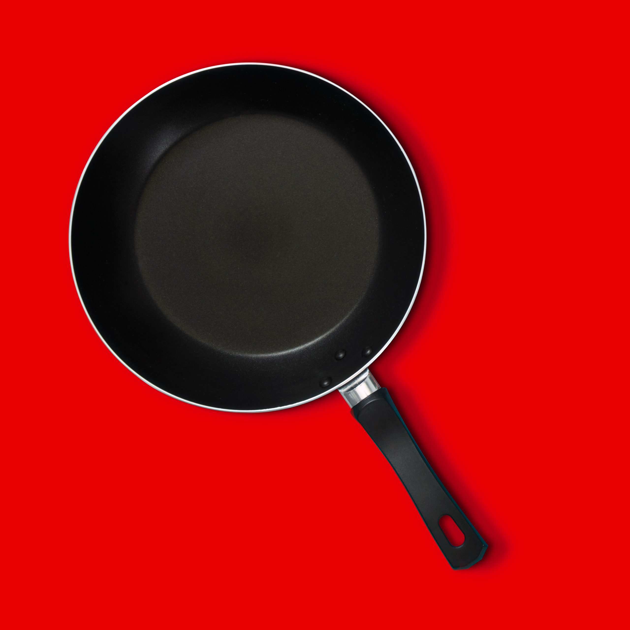 Non-stick pan over red background